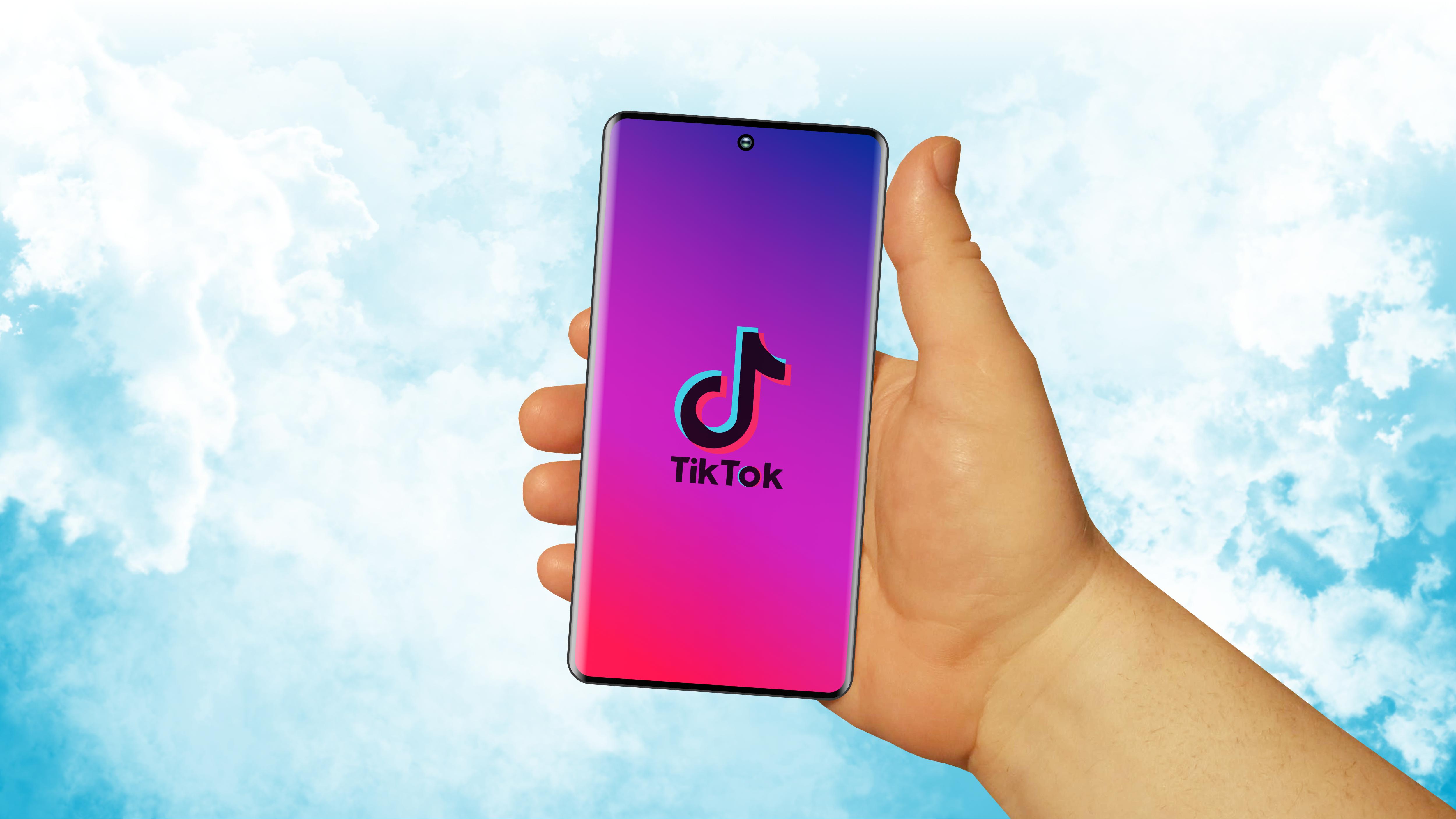 Download von iXimus.de: Symbolbild Verbot TikTok App, USA, Smartphone, Hand, blauer Himmel, #000291-2-4